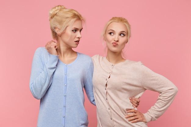 Portret van schattige tweelingen blondjes, een van de zussen is ondeugend en grimassen en de tweede kijkt haar afkeurend aan. staat op roze achtergrond. mensen en emoties concept.