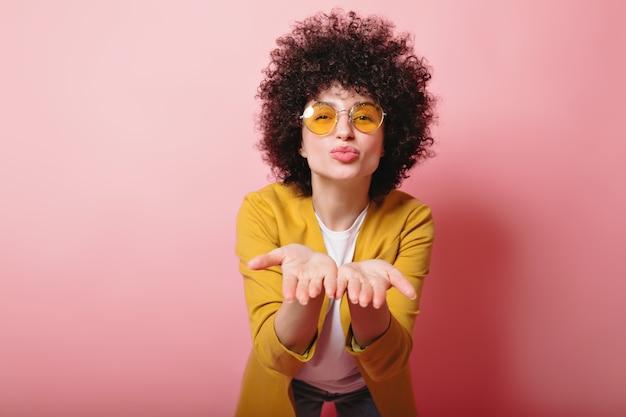 Portret van schattige vrouw met kort krullend haar gekleed geel jasje en gele bril stuurt een kus op roze