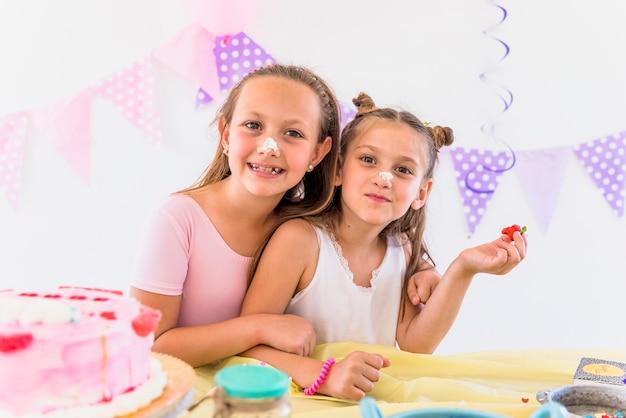 Portret van schattige zussen met taart op hun neus genieten in verjaardagsfeestje