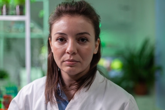 Portret van scheikundige vrouw in witte jas die werkt in farmaceutisch laboratorium