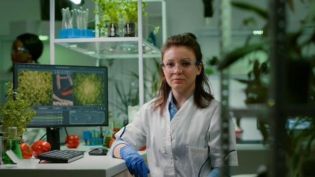 Portret van scheikundige vrouw in witte jas werken in farmaceutisch laboratorium