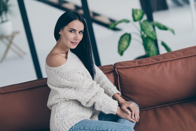 Portret van schitterend meisje zit op divan poseren slijtage casual stijl outfit denimjeans
