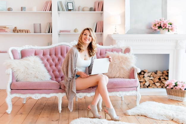 Portret van schitterende blondevrouw met laptop die thuis werken.