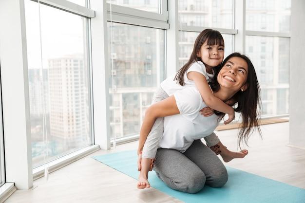 Portret van schitterende familiemoeder en kind die pret hebben en op de rug geven, terwijl thuis het doen van sportoefeningen op yogamat