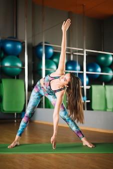 Portret van schitterende jonge vrouw het praktizeren yoga binnen