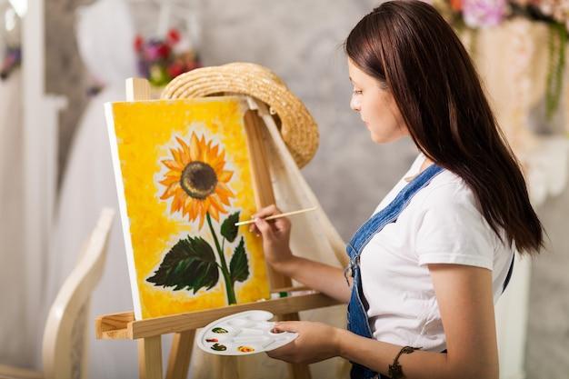 Portret van schitterende vrouwenkunstenaar die thuis schilderen