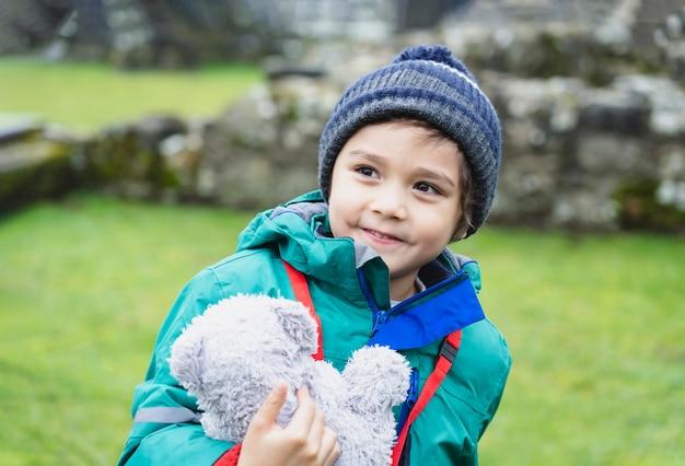 Portret van schooljong geitje dat teddybeer neemt onderzoekt met zijn leergeschiedenis