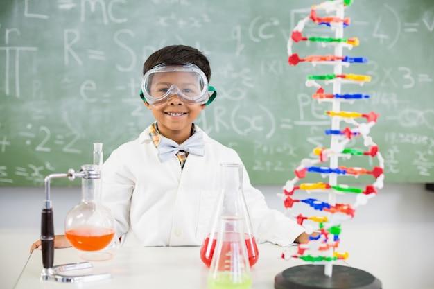 Portret van schooljongen die een chemisch experiment in laboratorium doet