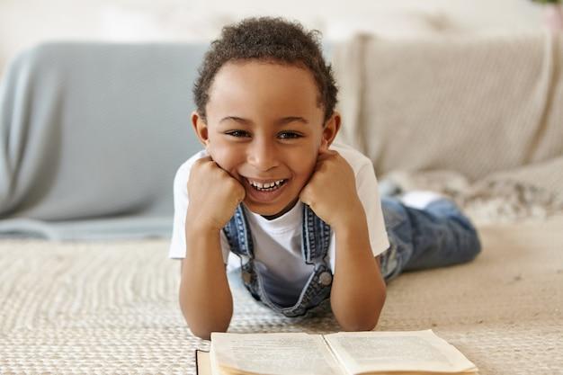 Portret van schooljongen die op vloer ligt en een boek in bibliotheek op school leest.