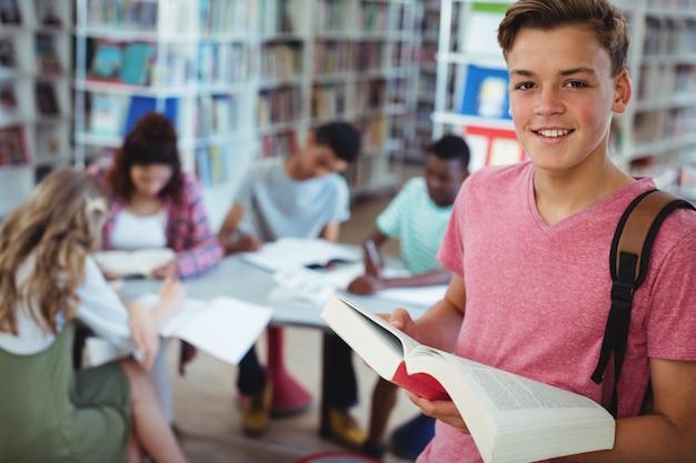 Portret van schooljongen met boek met zijn klasgenoten studeren