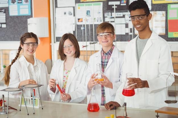 Portret van schoolkinderen die een chemisch experiment in laboratorium doen