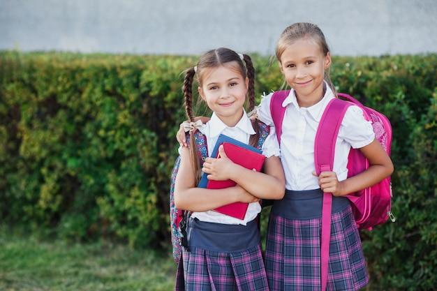 Portret van schoolkinderen met rugzak en boeken na school. begin van de lessen. eerste herfstdag.