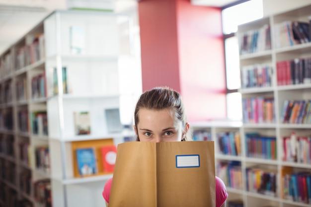 Portret van schoolmeisje dat haar gezicht met boek in bibliotheek verbergt