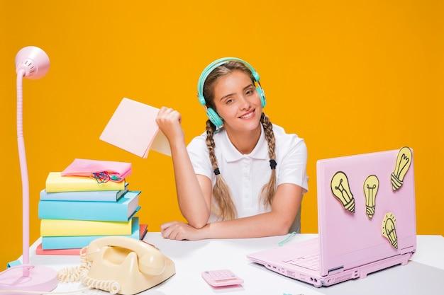 Portret van schoolmeisje dat met laptop bestudeert