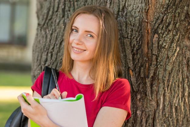 Portret van schoolmeisje dat tegen boom leunt