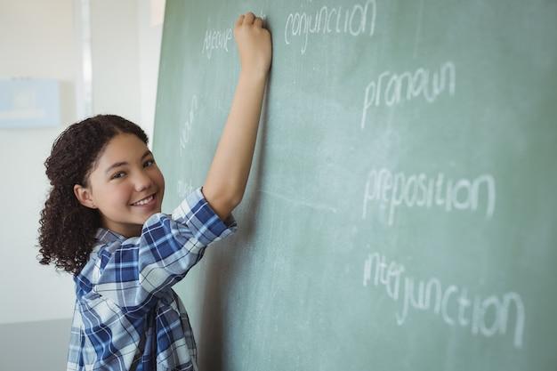 Portret van schoolmeisje die een leraar in klaslokaal beweren te zijn