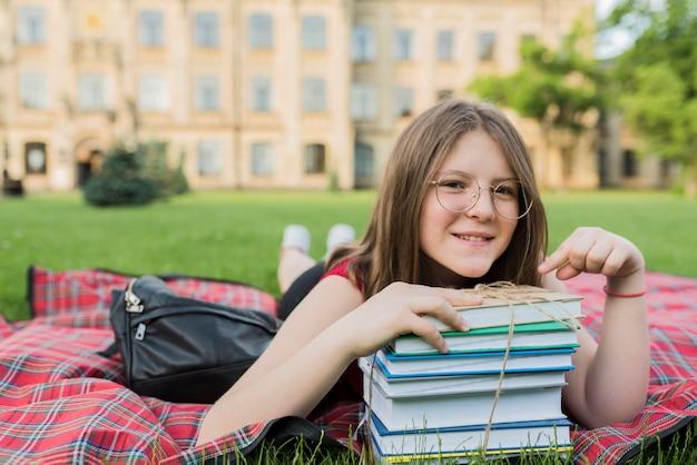 Portret van schoolmeisje die op deken met boeken leggen