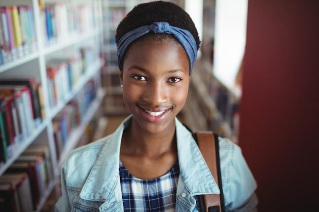 Portret van schoolmeisje glimlachend in bibliotheek