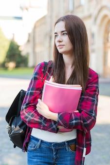 Portret van schoolmeisje met boek in stad