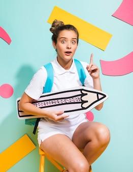 Portret van schoolmeisje met groot potlood