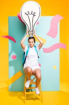 Portret van schoolmeisje met grote gloeilamp