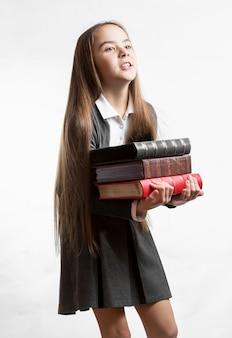 Portret van schoolmeisje met zware stapel boeken tegen een witte achtergrond