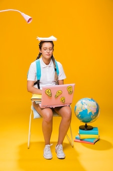 Portret van schoolmeisje op gele achtergrond