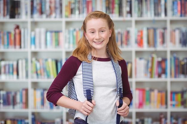 Portret van schoolmeisje permanent met schooltasje in bibliotheek