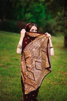 Portret van schoonheid indiase model met lichte make-up die haar gezicht achter de sluier verbergt. jonge hindoe vrouw met mehndi tatoeages van zwarte henna op haar handen