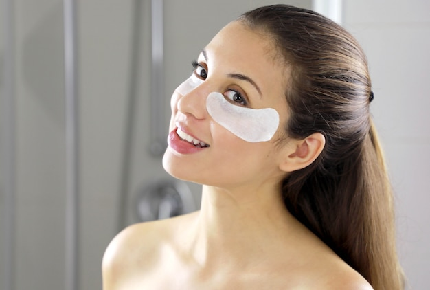 Portret van schoonheid vrouw met ooglapjes onder ogen in de badkamer.