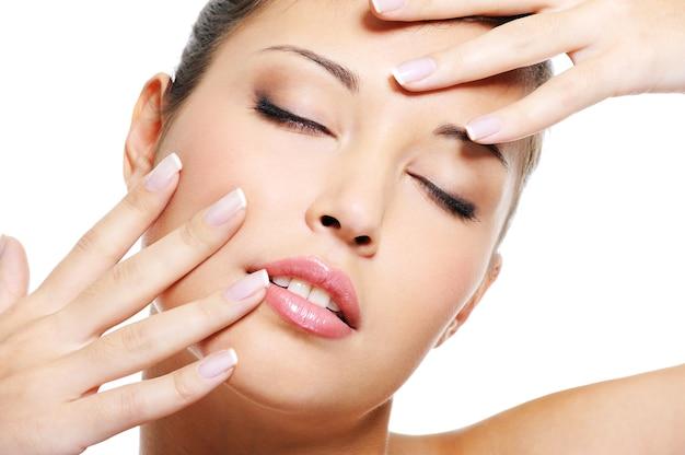 Portret van schoonheids aziatisch wijfje met elegante mooie vingernagels dichtbij haar gezicht