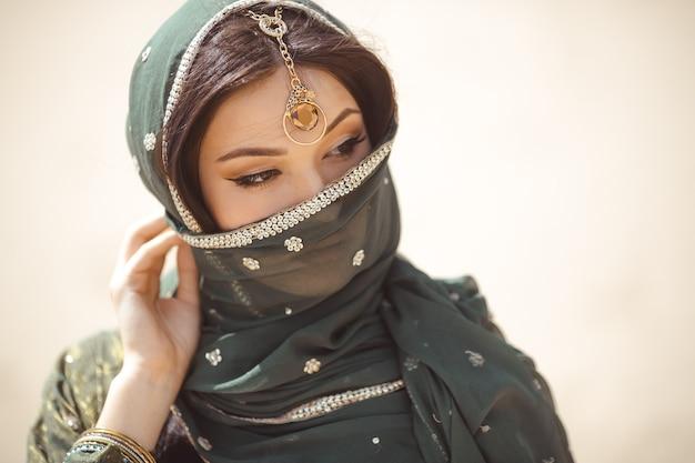 Portret van schoonheids indisch model met lichte samenstelling die haar gezicht achter de sluier verbergt die zich over gouden woestijnachtergrond bevindt.