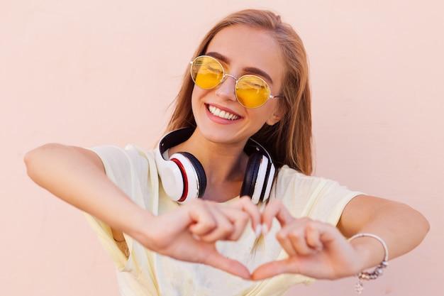 Portret van schoonheidsmanier die jonge vrouwen met gele zonnebril, hoofdtelefoons glimlachen