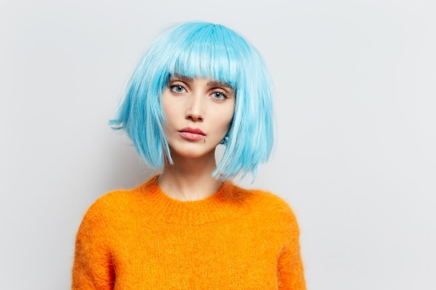 Portret van schoonheidsmeisje met blauw haar in oranje sweater op witte muur