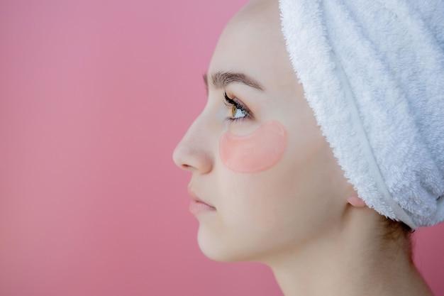 Portret van schoonheidsvrouw met oogflarden op roze achtergrond. vrouw schoonheid gezicht met masker onder de ogen. huidverzorging, cosmetisch product concept met kopie ruimte