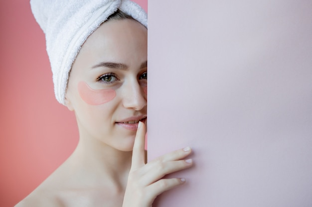Portret van schoonheidsvrouw met oogflarden op roze achtergrond. vrouw schoonheid gezicht met masker onder de ogen. huidverzorging, cosmetisch product concept