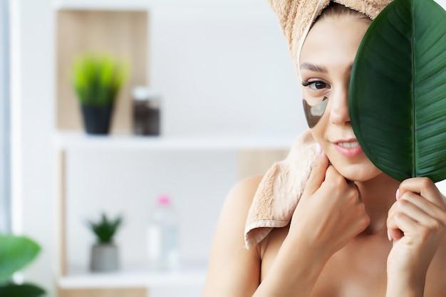 Portret van schoonheidsvrouw met ooglapjes die een effect van perfecte huid tonen.