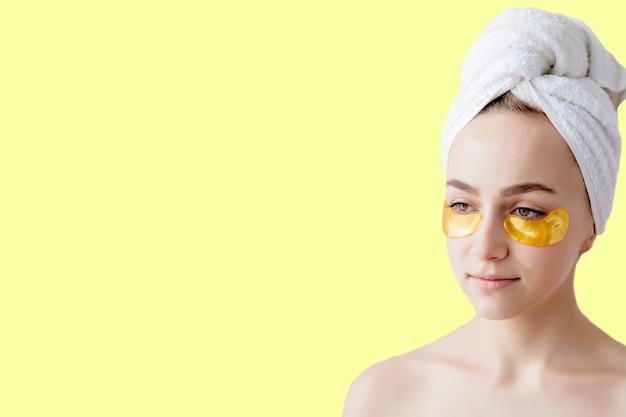 Portret van schoonheidsvrouw met ooglapjes op gele achtergrond.