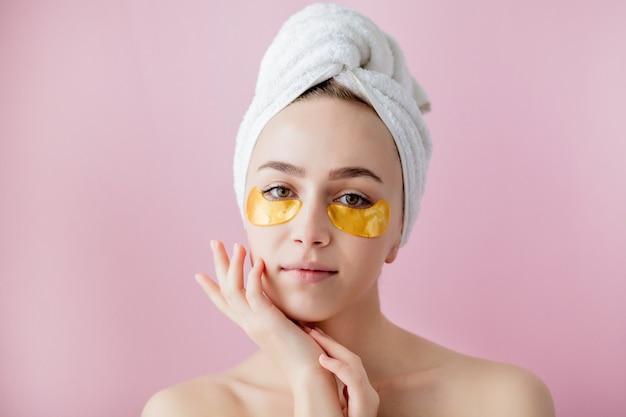 Portret van schoonheidsvrouw met ooglapjes op roze achtergrond.