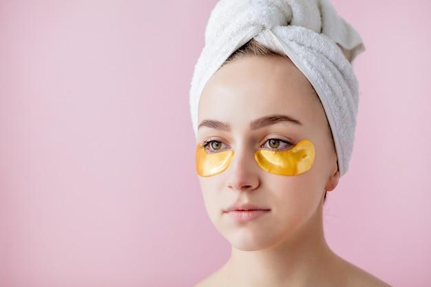 Portret van schoonheidsvrouw met ooglapjes op roze ruimte