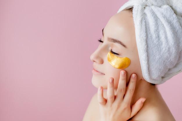 Portret van schoonheidsvrouw met ooglapjes op roze. vrouw schoonheid gezicht met masker onder de ogen.