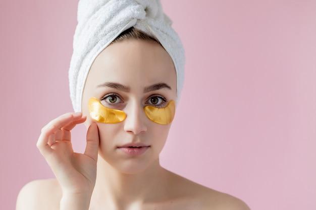 Portret van schoonheidsvrouw met ooglapjes. vrouw schoonheid gezicht met masker onder de ogen. mooie vrouw met natuurlijke make-up en gouden cosmetica collageenpleisters op frisse gezichtshuid