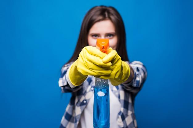 Portret van schoonmaakster gericht spray fles voor haar geïsoleerd