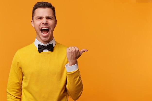 Portret van schreeuwen in opwinding aantrekkelijke man gekleed gele trui en vlinderdas, wijst met duim