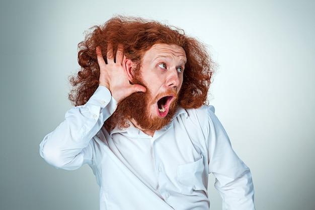 Portret van schreeuwende jonge man met lang rood haar en geschokte gelaatsuitdrukking op grijze achtergrond