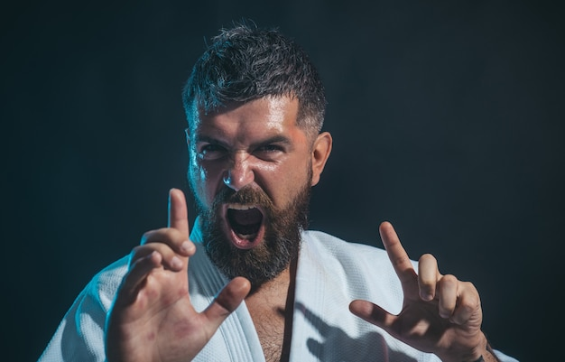 Portret van schreeuwende karate hoofdinstructeur karate man in actie karate vechter die kick laat zien
