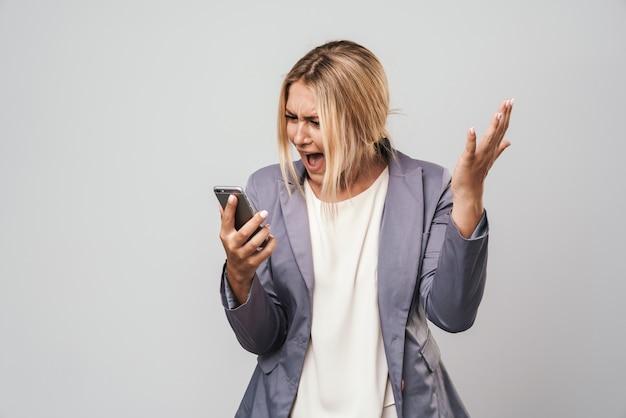 Portret van schreeuwende ontevreden gestresste verwarde jonge mooie vrouw poseren geïsoleerd over grijze muur met behulp van mobiele telefoon