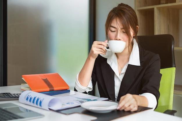 Portret van secretaresse die hete koffie drinkt vóór het werk