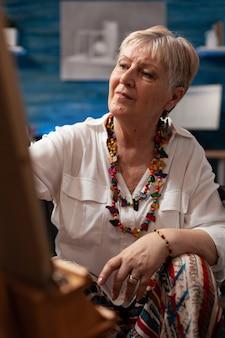 Portret van senior artiest zittend in rolstoel in studio