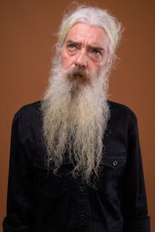 Portret van senior bebaarde man denken en opzoeken